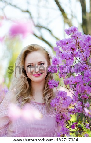 Beautiful blond woman among the spring flowering branches - stock photo