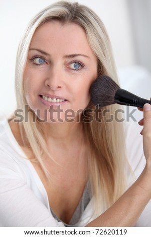 Beautiful blond woman applying makeup on her face - stock photo