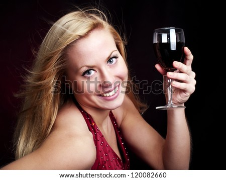 beautiful blond woman celebrating new year eve champagne over dark background