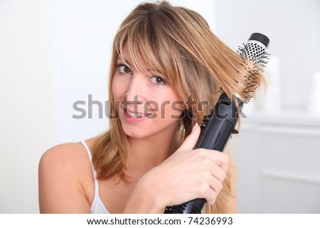 Beautiful blond woman curling her hair - stock photo