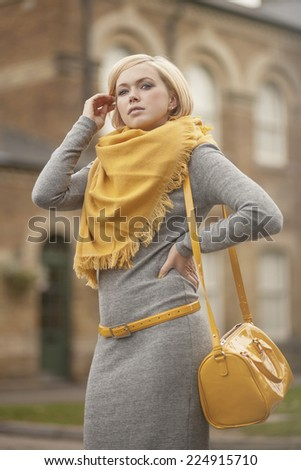 beautiful blond woman dressed in grey with yellow accessories - stock photo