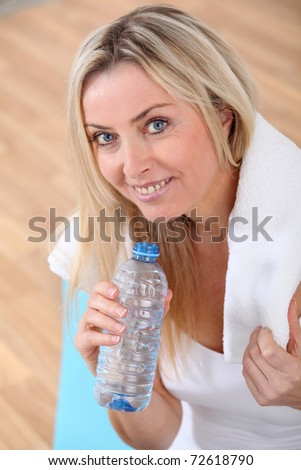Beautiful blond woman drinking water after exercising