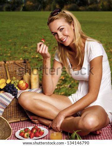 Beautiful blond woman enjoying a pick nick outdoors. Pick nick for one. - stock photo