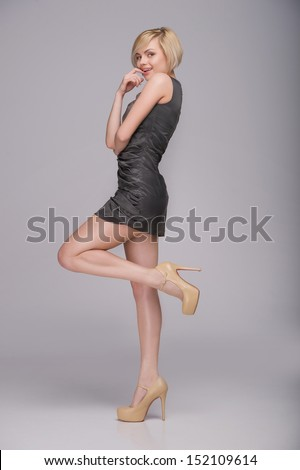 Beautiful blond woman. Full length of beautiful young woman posing and smiling while standing isolated on grey - stock photo