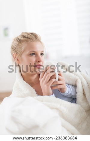 Beautiful blond woman holding a cup of tea lying on a couch, wrapped in a white blanket - stock photo