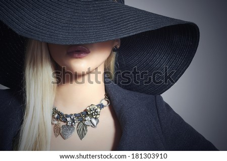 Beautiful Blond Woman in Black Hat. Close-up. Elegance Beauty Girl.Spring Shopping. Accessories. Lady in Jewelry - stock photo
