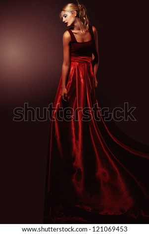 Beautiful blond woman in elegant red dress. Professional makeup and hairstyle