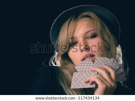 Beautiful blond woman in hat biting poker cards on black background - stock photo