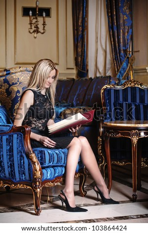 Beautiful blond woman in lacy dress sitting in blue armchair and reading menu book in luxury interior - stock photo