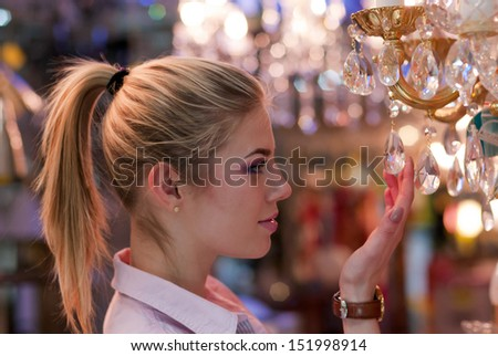 Beautiful blond woman in lamp shop - stock photo