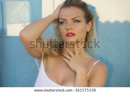 beautiful blond woman in lingerie on a terrace by the sea in summer - stock photo
