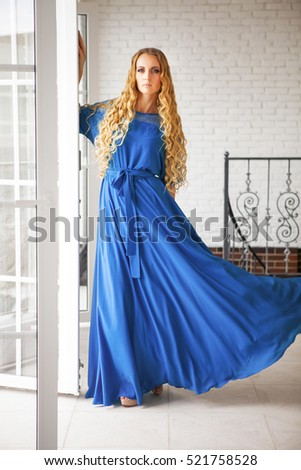 Beautiful blond woman in long blue dress near the stairs