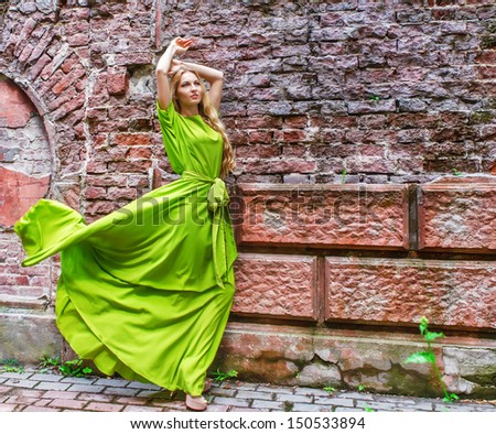 Beautiful blond woman in long green dress outdoors  - stock photo