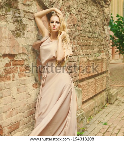 Beautiful blond woman in long green dress outdoors