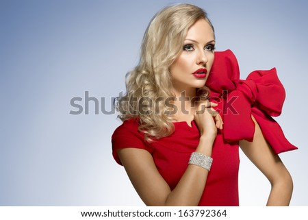 beautiful blond woman in red dress with nice hair style and a big bow on shoulder. she looks somewhere with surprise expression - stock photo