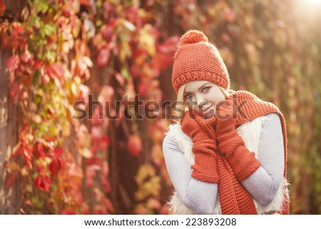 beautiful blond woman in red knitted scarf hat and gloves posing against colorful grape leaves - stock photo