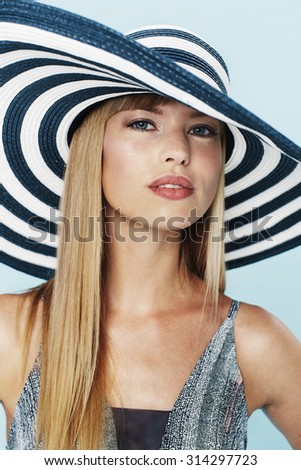 Beautiful blond woman in striped hat, portrait
