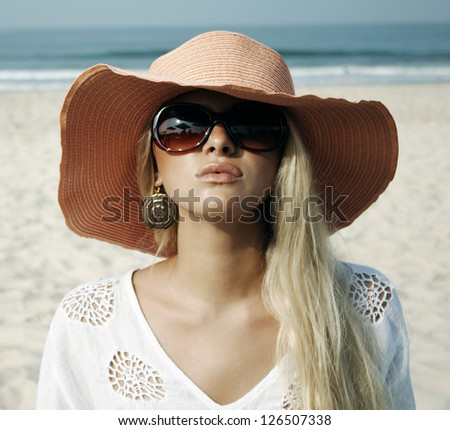 beautiful blond woman in the hat on the beach - stock photo