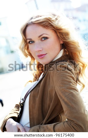 Beautiful blond woman in town by sunny day - stock photo