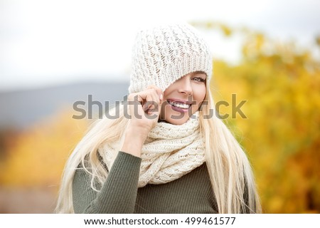 Beautiful blond woman in yellow autumn leaves.  Autumn. Young happy woman walking outdoors in autumn