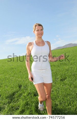 Beautiful blond woman jogging in country field - stock photo