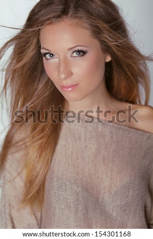 Beautiful Blond Woman. Long brown hair. Fashion model posing at studio. Health care.  Beauty girl with natural make-up.