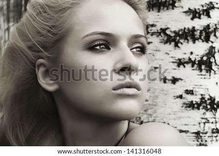 Beautiful blond woman near a tree in a forest - stock photo