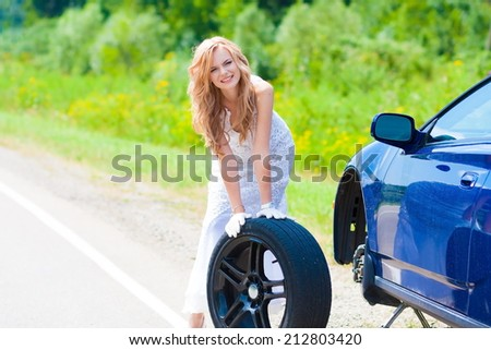 beautiful blond woman near car and wheel tire