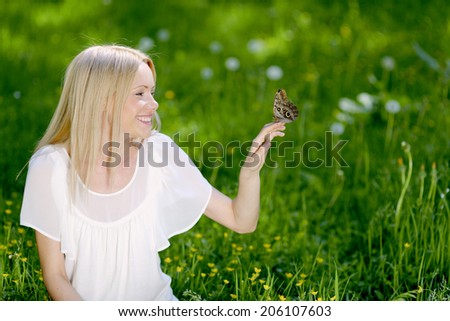 Beautiful blond woman playing with butterfly in spring park