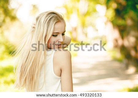 beautiful blond woman posing in sunlight, toned image