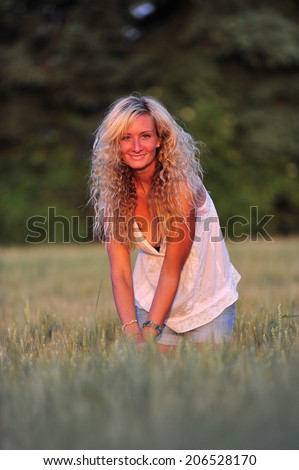 beautiful blond woman posing on a meadow in the twilight - stock photo