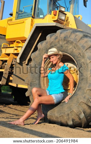 beautiful blond woman posing on a tire during the twilight - stock photo