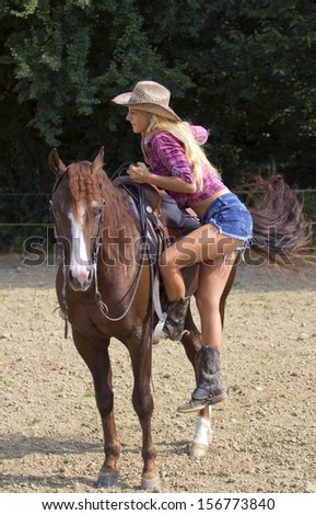 Beautiful blond woman pulling herself on the horse. - stock photo