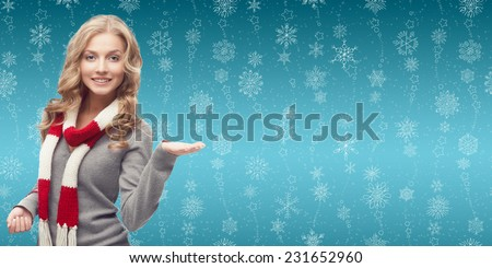 beautiful blond woman showing empty space over winter snowflakes background - stock photo