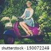 Beautiful blond woman sitting on a retro roller  - stock photo