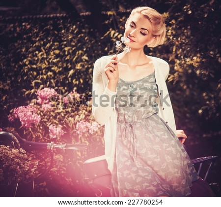 Beautiful blond woman sitting on a retro roller  - stock photo