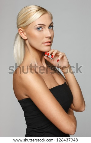 Beautiful blond woman standing with hand on chin at the camera over gray background