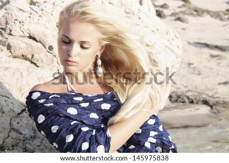 beautiful blond woman. stone.blue polka dot scarf