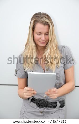 Beautiful blond woman using touchpad on grey background - stock photo