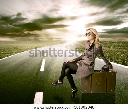 Beautiful blond woman waiting on road, concept of travel - stock photo