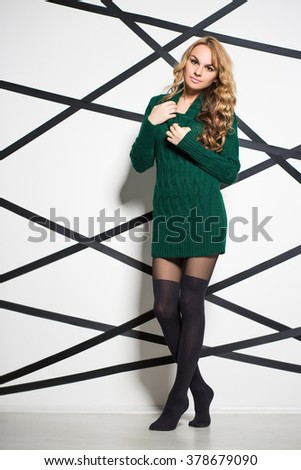 Beautiful blond woman wearing green knitted dress posing in the studio - stock photo