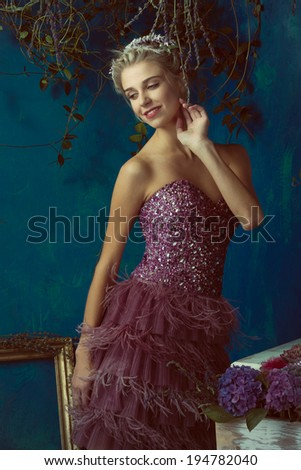 Beautiful blond woman with braid hairstyle and natural makeup. Wearing ping bohemian sequin and feather dress. Against blue grunge background - stock photo