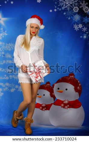Beautiful blond woman with christmas gift on xmas background. - stock photo
