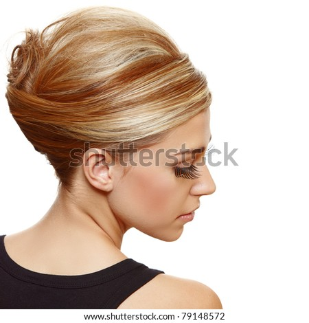 beautiful blond woman with false long eyelashes wearing hair in a classic french roll updo style. - stock photo