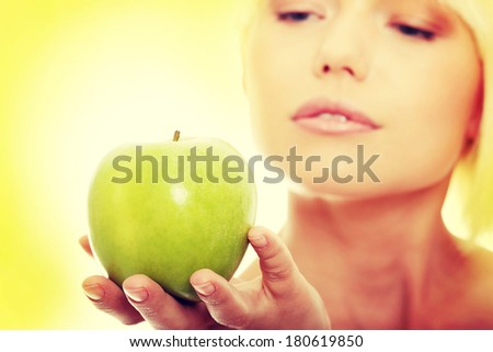 Beautiful blond woman with green apple. Over abstract green background  - stock photo