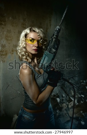 Beautiful blond woman with heavy drill in her hands