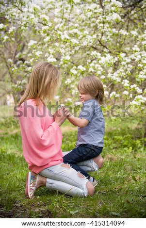 Beautiful blond woman with her little adorable kid boy in the blooming park on a sunny spring day. Happy mother with her son sitting on the green grass and enjoying flowers. Mum and child outdoors - stock photo