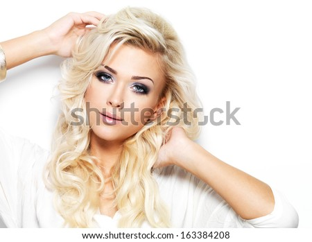 Beautiful blond woman with long curly hair and style makeup. Girl posing on white background - stock photo