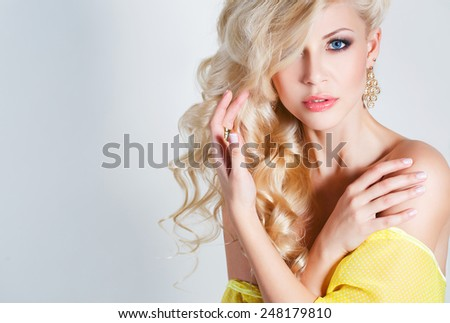 Beautiful blond woman with long curly hair - isolated on white. Portrait of young beautiful woman with long blond hair. Pretty woman in beautiful sexy yellow dress - stock photo
