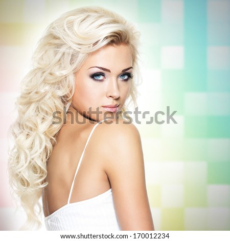 Beautiful blond woman with long curly hair over art background - stock photo